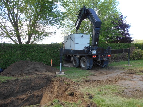 Septic box being set in hole with boom